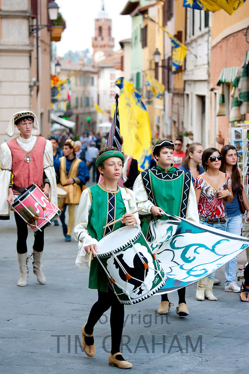 Contrada members in livery costumes for traditional parade in Asciano, inTuscany, Italy