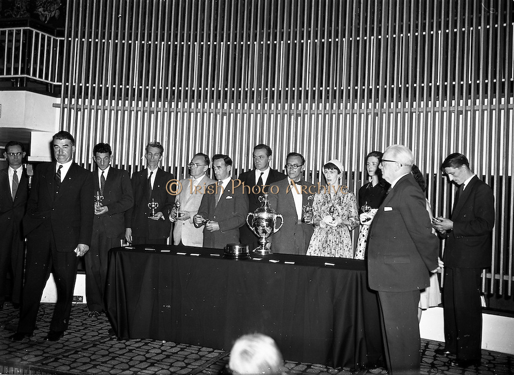 """27/05/1959<br /> 05/27/1959<br /> 27 May 1959<br /> Presentation of Esso Perpetual Trophy to the Listowel Drama Group at the Shelbourne Hotel, Dublin. The trophy and replicas for the  All Ireland Amateur Dram festival were presented by Mr. T.F. Laurie, Chairman and Managing Director of Esso Petroleum Co. (Ireland) Ltd. at a special luncheon. The Listowel group won the competition with their performance of the 3 Act play """"Sive"""" by John B. Keane. Picture shows Mr Bryan McMahon (2nd from left), President of the Listowel Drama Group replying to Mr. T.F. Laurie (2nd from right), after the presentation. In the rear of the photo with their replica trophies are (l-r): Brendan Carroll (Producer); John B. Keane (author of """"Sive""""); John Flaherty; Hilery Neilson; Brian Brennan; Kevin O'Donovan; William Kearney; Siobhan Cahill; Nora Relihan; Margaret Dillon (behind Mr. Laurie) and Sean Cahill."""