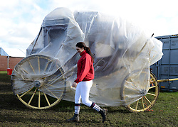 © Licensed to London News Pictures. 11/05/2012. Windsor, UK. A woman walks past a carriage wrapped up in plastic against the weather. The Royal Windsor Horse Show in Windsor, England on May 11 2012. Photo credit : Stephen Simpson/LNP