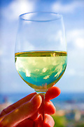 A hand holding a glass of white wine against the sky