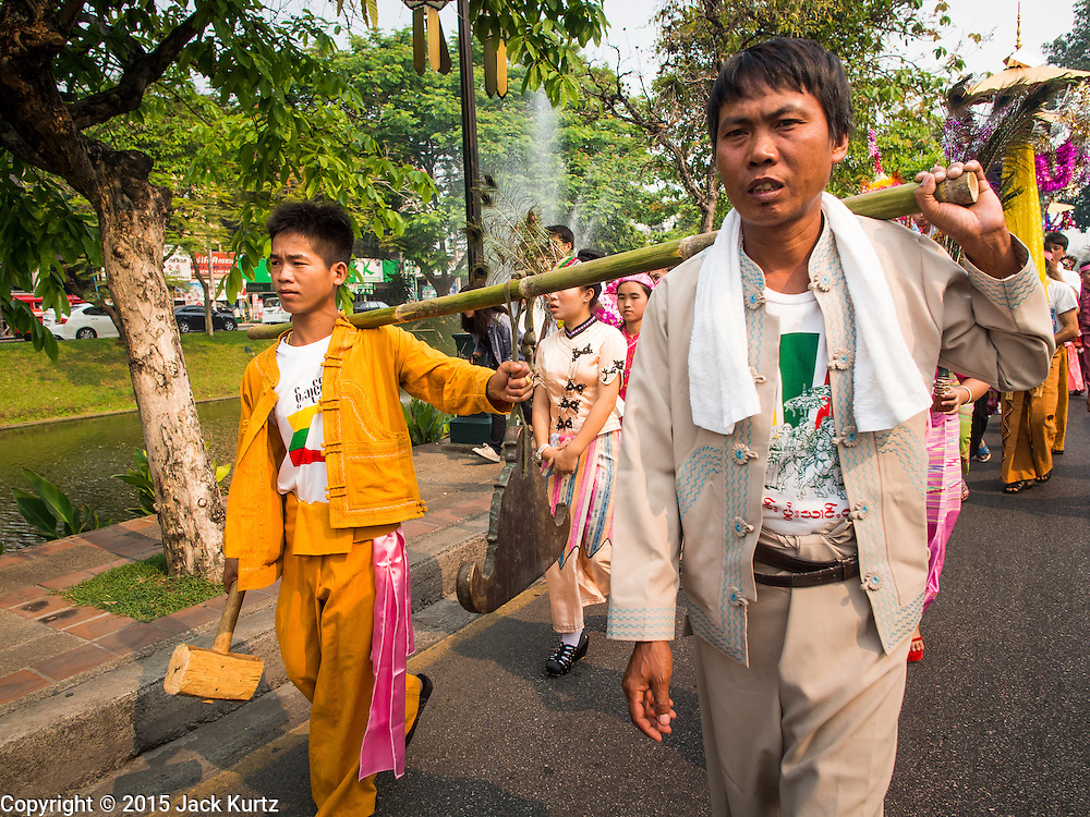"""05 APRIL 2015 - CHIANG MAI, CHIANG MAI, THAILAND: Men carry a gong that announces the arrival of a parade of Buddhist novices in Chiang Mai during the second day of the three day long Poi Song Long Festival in Chiang Mai. The Poi Sang Long Festival (also called Poy Sang Long) is an ordination ceremony for Tai (also and commonly called Shan, though they prefer Tai) boys in the Shan State of Myanmar (Burma) and in Shan communities in western Thailand. Most Tai boys go into the monastery as novice monks at some point between the ages of seven and fourteen. This year seven boys were ordained at the Poi Sang Long ceremony at Wat Pa Pao in Chiang Mai. Poy Song Long is Tai (Shan) for """"Festival of the Jewel (or Crystal) Sons.    PHOTO BY JACK KURTZ"""