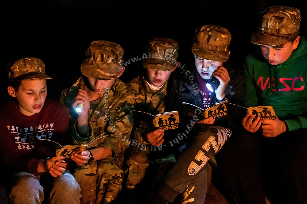 Boys participating to the ultra-nationalistic Azovets children's camp are reading and singing songs written on their induction book while sitting together around the evening fire, on the banks of the Dnieper river in Kiev, Ukraine's capital.