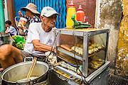 """12 APRIL 2012 - HO CHI MINH CITY, VIETNAM:  A grilled meat vendor on a street in Cholon, the Chinese-influenced section of Ho Chi Minh City (former Saigon). It is the largest """"Chinatown"""" in Vietnam. Cholon consists of the western half of District 5 as well as several adjoining neighborhoods in District 6. The Vietnamese name Cholon literally means """"big"""" (lon) """"market"""" (cho). Incorporated in 1879 as a city 11km from central Saigon. By the 1930s, it had expanded to the city limit of Saigon. On April 27, 1931, French colonial authorities merged the two cities to form Saigon-Cholon. In 1956, """"Cholon"""" was dropped from the name and the city became known as Saigon. During the Vietnam War (called the American War by the Vietnamese), soldiers and deserters from the United States Army maintained a thriving black market in Cholon, trading in various American and especially U.S Army-issue items.        PHOTO BY JACK KURTZ"""