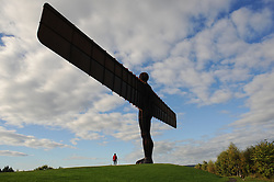 © Licensed to London News Pictures. <br /> 24/09/2014. <br /> <br /> Gateshead, United Kingdom<br /> <br /> A woman walks her dog next to the Angel of the North sculpture in Gateshead.<br /> <br /> <br /> Photo credit : Ian Forsyth/LNP