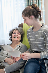 Granddaughter showing old photos to grandmother in rest home