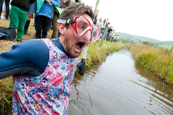 © Licensed to London News Pictures. 27/08/2017. Llanwrtyd Wells, Powys, Wales, UK. The water in the bog is very cold! The 32nd annual World Bog Snorkelling Championships, conceived over 30 years ago in a Welsh pub by landlord Gordon Green, are held at the Waen Rhydd Bog. Using unconventional swimming strokes, participants swim two lengths of a 55 metre trench cut through a peat bog wearing snorkel mask and flippers. Photo credit: Graham M. Lawrence/LNP