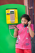 Young girl wearing brightly coloured clothes makes a call on a pay phone while looking at her cell phone. Old and new modes of communication. Beijing, China.