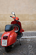 Red Vespa motor scooter street scene in the historic hill town of Spoleto, Umbria, Italy.