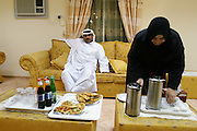 A family in Dubai offers drinks and food to visitors in their home, United Arab Emirates. As an indigenous citizen of the United Arab Emirates this man's family is entitled to a substantial subsidy from the government and jobs for the males in the household. Their high standard of living is a far cry from his parents' life as nomadic Bedouin camel herders of the desert. Dubai, United Arab Emirates.