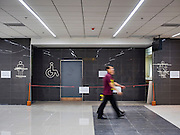 """24 DECEMBER 2015 - BANGKOK, THAILAND: People walk past uncompleted and unopen bathrooms in the new domestic terminal at Don Muang (also spelled Don Mueang) International Airport. The new terminal had its """"soft"""" opening Dec. 24. Don Muang is the airport used by low cost airlines serving Bangkok and is now the largest airport in the world for low cost carriers. In 2014, more than 21million passengers used Don Muang. Don Muang International Airport is the oldest airport in Asia and one of the oldest airports in the world. It started functioning as an airfield in 1914.     PHOTO BY JACK KURTZ"""