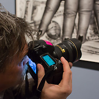 Photographer takes a photo at the exhibition of american fashion photographer Helmut Newton in Budapest, Hungary on April 02, 2013. ATTILA VOLGYI