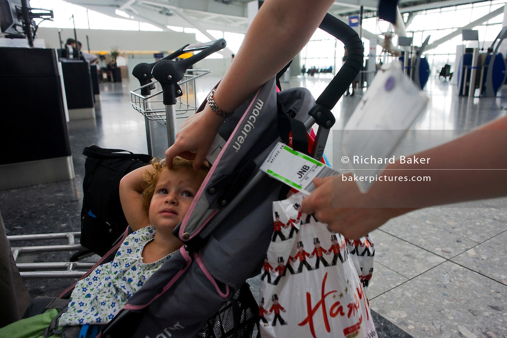 Young girl sits in pushchair as a child-friendly British Airways check-in lady attaches airline tag at Heathrow Airport's T5