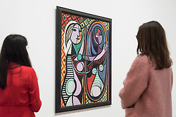 "© Licensed to London News Pictures. 06/03/2018. LONDON, UK.  Visitors view ""Girl Before a Mirror (Jeune Fille devant un miroir)"", 1932, by Pablo Picasso. Preview of ""Picasso 1932 - Love, Fame, Tragedy"", the Tate Modern's first ever solo exhibition of the work of Pablo Picasso.   More than 100 paintings, sculptures and works on paper covering the year 1932, a pivotal time in Picasso's life, are on display 8 March to 9 September 2018. Photo credit: Stephen Chung/LNP"