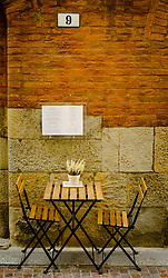 Table and chairs outside a restaurant in the Via de' Toschi, Bologna, Italy<br /> <br /> (c) Andrew Wilson | Edinburgh Elite media