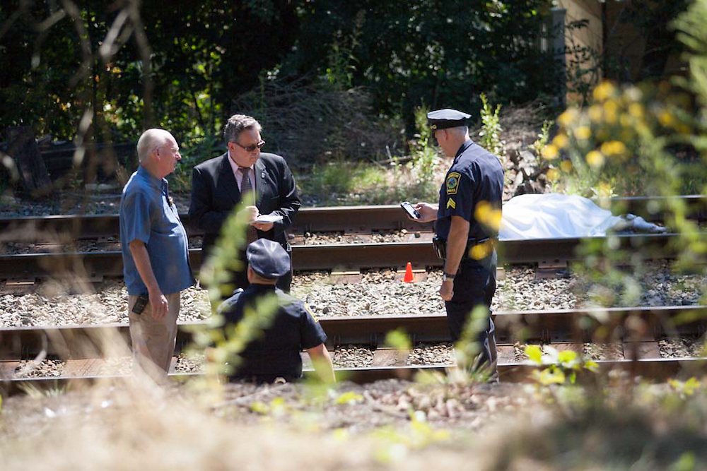 Norwood, MA 08/30/2012.***Editors note graphic content***<br /> Norwood and MBTA Police officers investigate the scene on the MBTA Franklin Line right-of-way where a pedestrian was struck and killed by an outbound train on Thursday morning near Everett Street.
