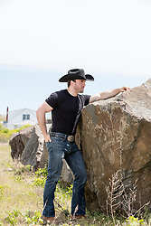 rugged good looking cowboy outdoors by a large rock