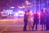 Orlando Police officers direct family members away from a multiple shooting at a nightclub in Orlando, Fla., Sunday, June 12, 2016. (AP Photo/Phelan M. Ebenhack)