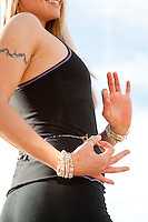 A woman's hands in yoga pose (mudra) outdoors.