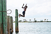 Young boys jump off pier pillions into the New Plymouth Harbour at New Plymouth, Green Turtle Cay, Bahamas.