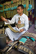 A traditional dagger seller sews a belt used for fastening the jambiya around the waist at his market stall in Sanaa, Yemen.