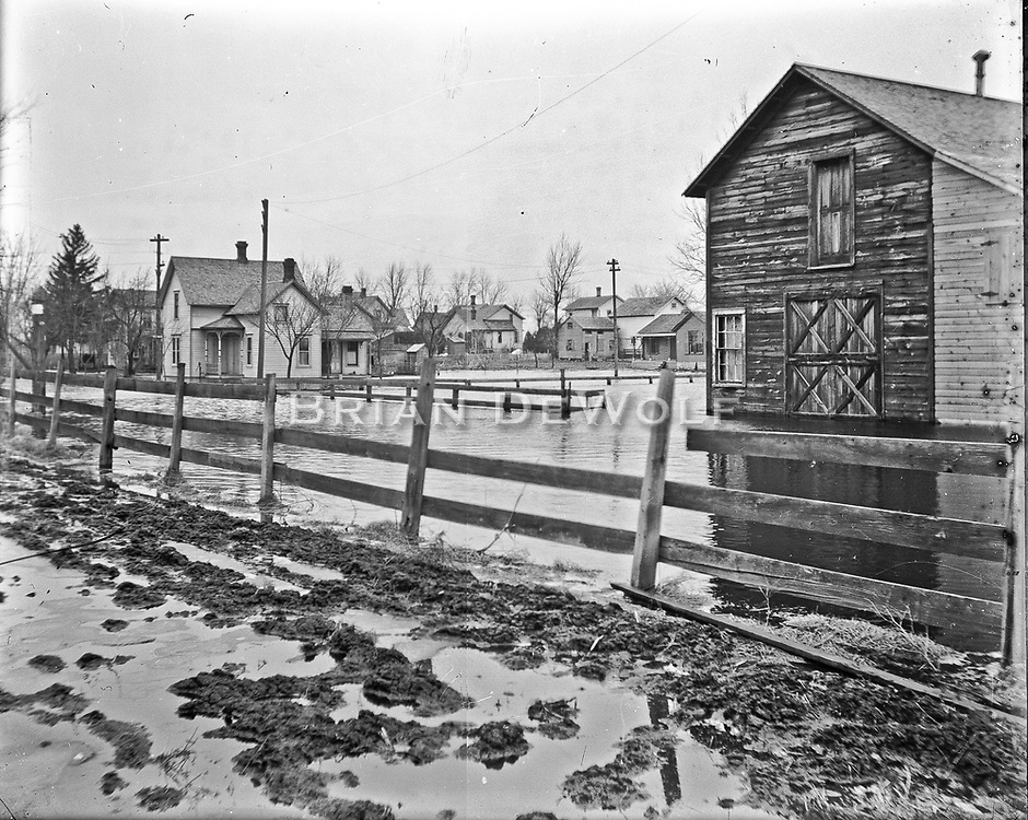 The water between the fence and the barn is Delia Street just south of State Street. The white house in the background is on the N.E. corner of Delia and State. The photographer's location would be very close to where the Burlington RR tracks meet the dead end of Delia St. Camera is facing north/northeas