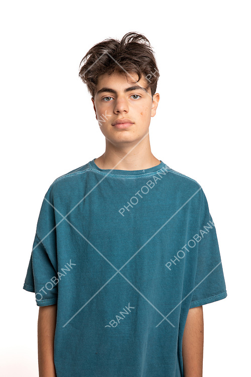 Portrait of young boy on white background standing alone front to the camera with all the problems of all teenagers.