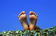 Two bare feet on a shingle beach against blue sky