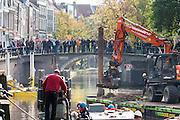 Mensen kijken naar de werkzaamheden bij de kademuur. In Utrecht is aan de Bemuurde Weerd een deel van een historische kademuur ingestort. De oorzaak is mogelijk dat door de heftige regenval eerder in de week een boom is omgevallen. Op dit moment wordt een nooddamwand geplaatst.<br /> <br /> In Utrecht at the Bemuurde Weerd a part of a historic quay collapsed . The possible cause is that the heavy rainfall earlier in the week a tree has fallen. At this moment emergency piling takes place.