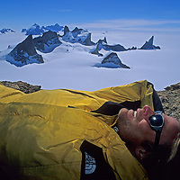 Conrad Anker relaxes atop Mount Kubus in Queen Maud Land, Antarctica.  The nearby Trolls Castle is in center background and Rakekniven (The Razor) on right.