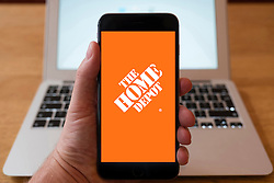 Using iPhone smartphone to display logo of Home Depot the chain of home improvement stores in the USA