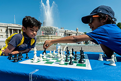 © Licensed to London News Pictures. 18/07/2021. LONDON, UK. Prayaan (L) and Kayan, both aged 8, play chess at Chess Fest in Trafalgar Square.  The event celebrates the game of chess and visitors can learn the game, play chess or challenge a Grandmaster.  Also, to celebrate the 150th anniversary of Lewis Carroll's Alice Through the Looking Glass book which featured the game of the chess, 32 actors dressed as Alice Through the Looking Glass characters stand on a giant chessboard replaying a game based on the book.  Photo credit: Stephen Chung/LNP