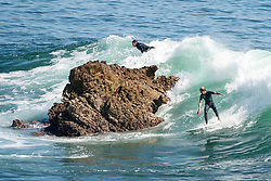 May 2, 2017 - Laguna Beach, CA, USA - Surfers ride waves right next to a rock at Laguna Beach on Tuesday, May 2, 2017. (Photo by Kyusung Gong/Orange County Register/SCNG) (Credit Image: © Kyusung Gong/The Orange County Register via ZUMA Wire)