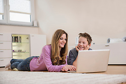 Mother and son lying on floor looking at laptop