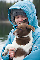 Portrait of young woman and puppy near lake.