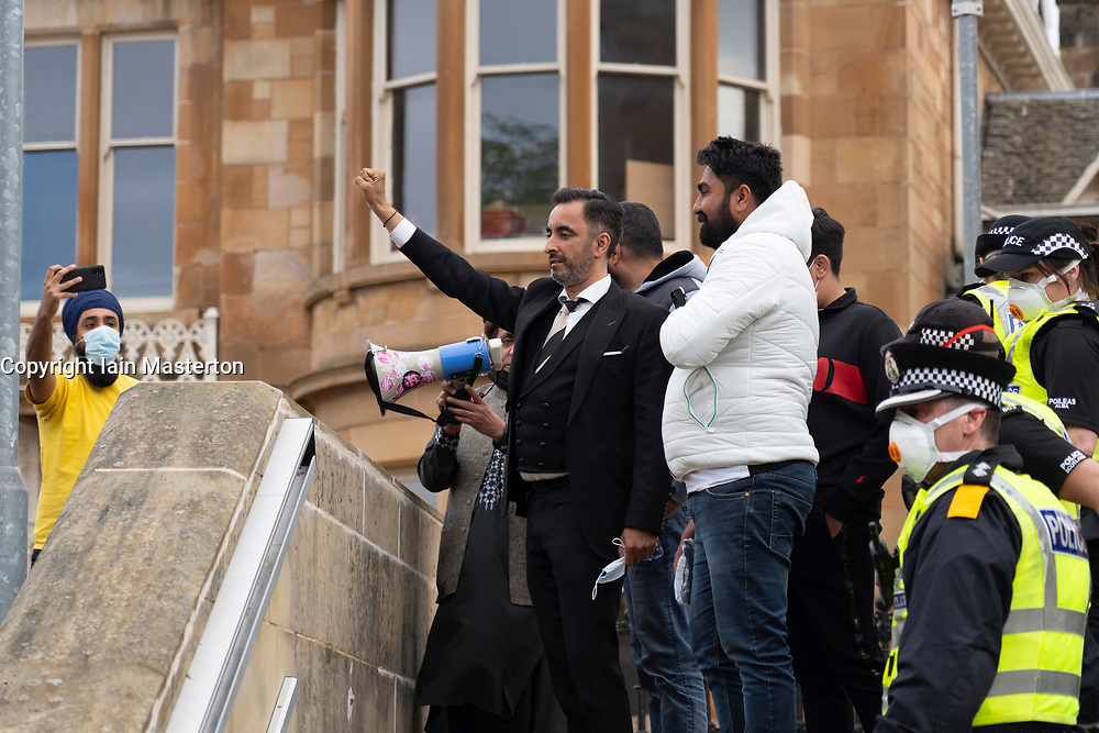 Glasgow, Scotland, UK. 13 May 2021.At approx 5.30 pm police released two men from a Home Office detention vehicle. Accompanied by lawyer Aamer Anwar the men walked to a nearby mosque surrounded by hundreds of police and supporters who had previously been surrounding the vehicle and sitting on the street..Two males and Aamer Anwar walk up steps of mosque to address supporters.  Iain Masterton/Alamy Live News