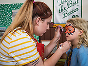 27 JUNE 2019 - CENTRAL CITY, IOWA: JES BIXBY, left, paints the face of ZEPHY ATKINS, 6, at the Linn County Fair. Summer is county fair season in Iowa. Most of Iowa's 99 counties host their county fairs before the Iowa State Fair, August 8-18 this year. The Linn County Fair runs June 26 - 30. The first county fair in Linn County was in 1855. The fair provides opportunities for 4-H members, FFA members and the youth of Linn County to showcase their accomplishments and talents and provide activities, entertainment and learning opportunities to the diverse citizens of Linn County and guests.      PHOTO BY JACK KURTZ