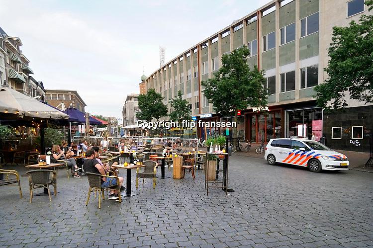 Nederland, Nijmegen, 1-6-2020  Vandaag, 1 juni, gaan de versoepelde coronamaatregelen in waardoor de horeca weer beperkt open kan en ook culturele instellingen openzoals musea open kunnen. Terrassen en tarrasjes mogen weer bezocht worden mits aan regels wordt voldaan om  het besmettingsrisico minimaal te maken. Een politieauto met politie komt voorbij om te handhaven of te waarschuwen . Unlock,beperkende,beperkingen, cafe, opheffen,versoepelen,versoepeling , opengooien,  openen,opening,opmeten,voorbereiden,voorbereiding, boa,handhaving,Foto: Flip Franssen