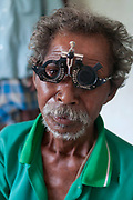 India. Orissa. T. Village eye camp at Fatak, near Sundergarh. September 2012. A man's eyes are tested to see what strength glasses he needs.