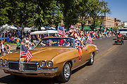 30 JUNE 2012 - PRESCOTT, AZ:  People in a flag festooned car at the Prescott Frontier Days Rodeo Parade. The parade is marking its 125th year. It is one of the largest 4th of July Parades in Arizona. Prescott, about 100 miles north of Phoenix, was the first territorial capital of Arizona.    PHOTO BY JACK KURTZ