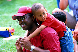 Stock photo of a small boy leaning over his father's shoulders