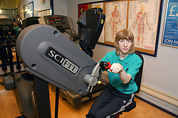 Woman using upper body ergometer at an inclusive fitness gym,