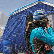 Melissa Arnot turns her back to the wind and snow blast generated by the avalanche as it blows through Basecamp.