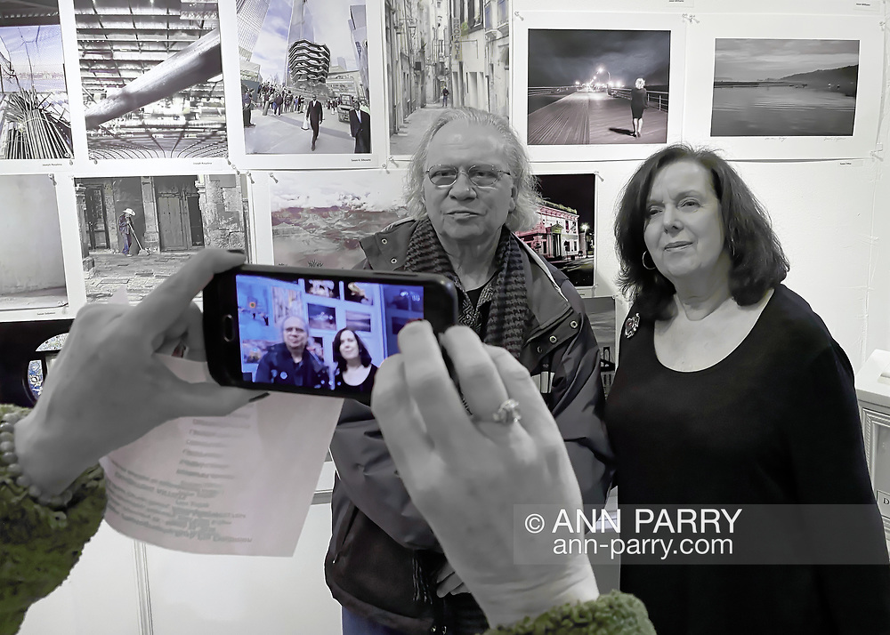 Huntington, New York, USA. February 29, 2020. L-R, a guest and SUSAN TIFFEN pose for cellphone photo as they stand under her photo 'Jones Beach Babe' - a Best of Show co-winner - at the fotofoto gallery during its reception for its 'Your Best Shot' Open Photography push-pin exhibition.