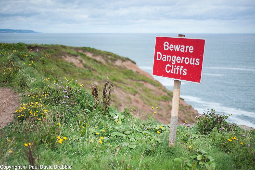 Dangerous Cliff Sign on the cleveland way footpath above the East coast Beaches and seafront Filey North Yorkshire.
