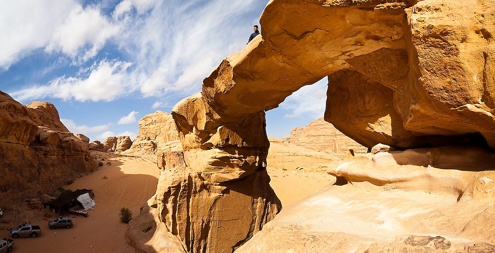 A Bedouin boy stands on the top of the Um Frouth Arch in Wadi Rum, Jordan.