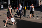 Strangers each carry their own bags on Cannon Street in the City of London, UK.