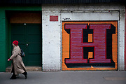 Woman walks past shop shutters in Aldgate, London are painted with the letters forming the word HAPPY. This kind of inspirational street art is commonplace around the outskirts of the city.