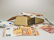 Goudstaaf met geld. | Gold bar with money