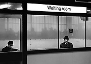 Waiting room Waterloo, 5.30pm. The flow of evening commmuters is reflected in the windows. Coming and Going is a project commissioned by the Museum of London for photographer Barry Lewis in 1976 to document the transport system as it is used by passengers and commuters using public transport by trains, tubes and buses in London, UK.