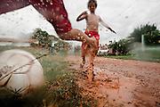 Garotos jogam futebol de rua, após uma forte chuva em Cuiabá, Mato grosso, Brasil.